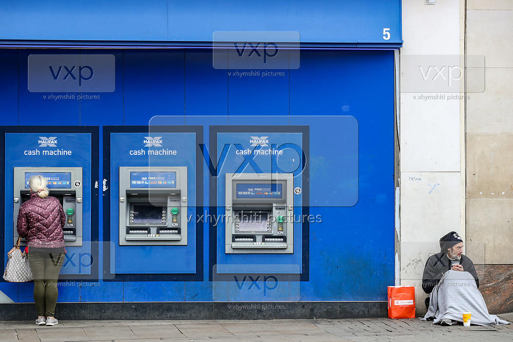 A woman collects her cash from a Halifax ATM in Manchester on Wednesday, April 28, 2021. Northern England welcomed the return of outdoor drinking and dining in April, but the easing of lockdown was also met with concerns about a lack of social distancing, and a wider sense of nervousness within the hospitality sector as businesses tried to operate at a significantly lower capacity and with some confusion over the rules. (Photo/ Vudi Xhymshiti)