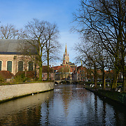 View of canal and Church of Our Lady from Begijnhof, Brugge, Belgium