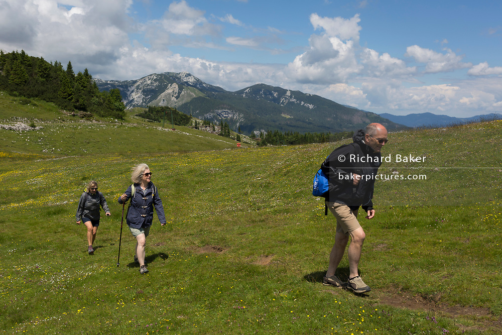 Walkers walk in Velika Planina, on 26th June 2018, in Velika Planina, near Kamnik, Slovenia. Velika Planina is a mountain plateau in the Kamnik–Savinja Alps - a 5.8 square kilometres area 1,500 metres (4,900 feet) above sea level. Otherwise known as The Big Pasture Plateau, Velika Planina is a winter skiing destination and hiking route in summer. The herders' huts became popular in the early 1930s as holiday cabins (known as bajtarstvo) but these were were destroyed by the Germans during WW2 and rebuilt right afterwards by Vlasto Kopac in the summer of 1945.