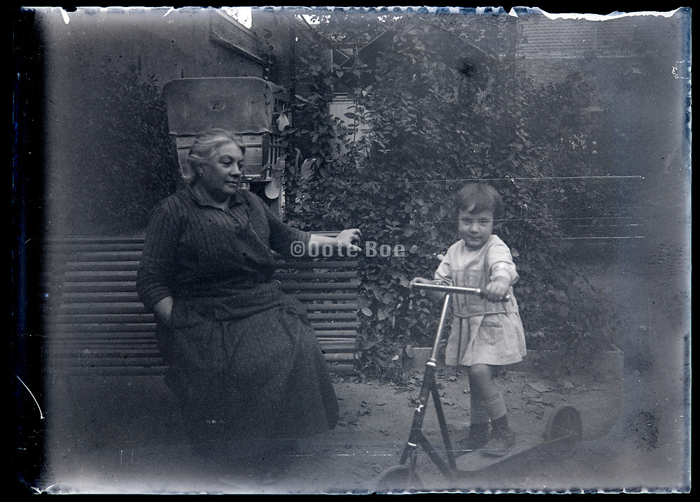 grandmother looking adorable at little child with step scooter France circa 1920s