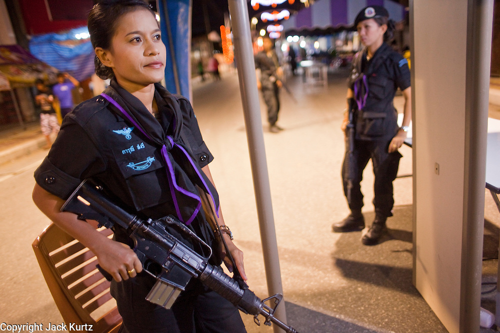 Sept. 29, 2009 -- YARANG, THAILAND: Members of the women's Ranger unit staff a checkpoint at the entrance to the night market in Yarang, Thailand, Sept. 29. The 39 women in the 44th Army Ranger Regiment are the only Thai women seeing front line active duty against Moslem insurgents in Thailand's deep south provinces of Pattani, Narathiwat and Yala. All of the other women serving in Thai security services are employed as office and clerical workers. The Ranger women are based at the Ranger camp in the Buddhist village of Baan Trokbon in Sai Buri district of Pattani province. The unit was formed in 2006 after Muslims complained about the way Thai soldiers, all men, treated Muslim women at roadblocks and during security sweeps. The women are frequently called upon to back up Thai regular army units when they are expected to encounter a large number of Muslim women. At least two of the women have been killed by Muslim insurgents. The unit has both Muslim and Buddhist members. Many of the women in the unit joined after either their fathers or husbands were killed by insurgents.  Photo by Jack Kurtz / ZUMA Press