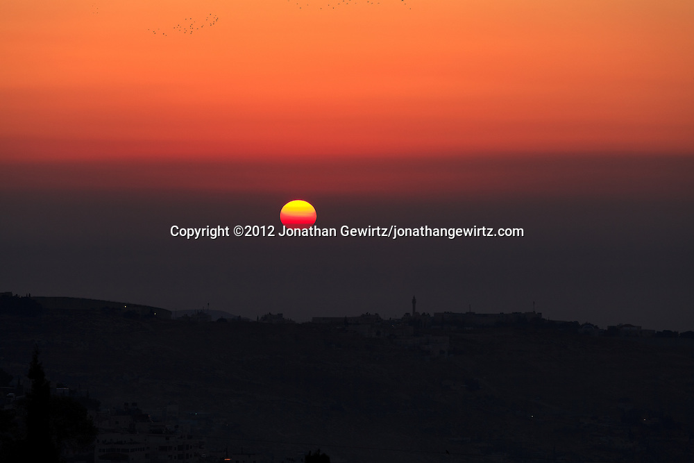 The sun rises over a minaret in the village of Abu Dis on the eastern outskirts of Jerusalem. WATERMARKS WILL NOT APPEAR ON PRINTS OR LICENSED IMAGES.