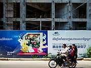 """13 FEBRUARY 2019 - SIHANOUKVILLE, CAMBODIA: A Cambodian family on a motorcycle passes Blue Bay resort and casino, a new resort being built by Chinese investors in Sihanoukville. There are about 80 Chinese casinos and resort hotels open in Sihanoukville and dozens more under construction. The casinos are changing the city, once a sleepy port on Southeast Asia's """"backpacker trail"""" into a booming city. The change is coming with a cost though. Many Cambodian residents of Sihanoukville  have lost their homes to make way for the casinos and the jobs are going to Chinese workers, brought in to build casinos and work in the casinos.      PHOTO BY JACK KURTZ"""