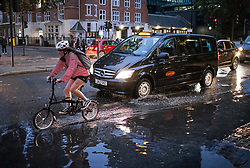 © Licensed to London News Pictures. 21/10/2021. London, UK. A cyclists ploughs through flood water on the Euston road in North London caused by heavy rain over night in the capital. Flash flooding hit parts of the south east as Storm Aurore brought winds of up to 45mph . Photo credit: Ben Cawthra/LNP