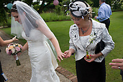 Mother of the bride inspects her daughter's new ring after a civil wedding ceremony in Essex, England. The older lady holds her daughter's hand and looks more intently at her newly placed wedding ring on the third finger, according to tradition. The mother also holds a glass of Pims, a well-liked drink of alcohol and fruit that helps refresh on a warm day. And wearing a very English piece of headwear is the 'fascinator' that perches on the side of the head. This European wedding has taken place inside a covered Orangery at a private wedding and event venue. Rather than marrying in a religious context, the happy couple have preferred to tie the knot in this popular setting for a non-church meaning.