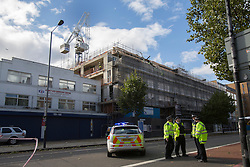 © licensed to London News Pictures. London, UK 28/10/2013. Police officers close Old Kent Road in south London as a crane collapsed on a building after the St Jude's Day Storm battered the capital with high winds on Monday, 28 October 2013. Photo credit: Tolga Akmen/LNP