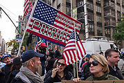 "New York, NY - 11 November 2019. New York City's Veterans Day Parade, today marking the 100th anniversary of the armistice ending the fighting of the first World War, was attended by a number of people protesting President Trump, who spoke at the opening ceremony, and a smaller number of pro-Trump supporters. Here a large American flag is overprinted with ""Impeachment is Patriotic"""
