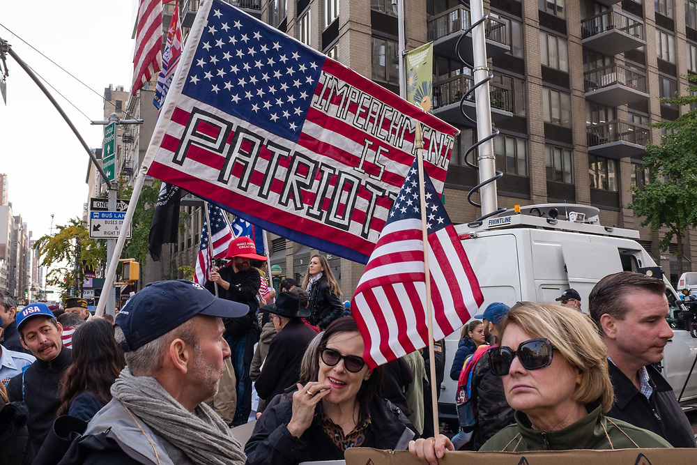 """New York, NY - 11 November 2019. New York City's Veterans Day Parade, today marking the 100th anniversary of the armistice ending the fighting of the first World War, was attended by a number of people protesting President Trump, who spoke at the opening ceremony, and a smaller number of pro-Trump supporters. Here a large American flag is overprinted with """"Impeachment is Patriotic"""""""