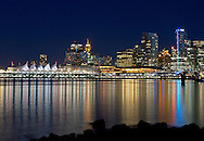The lights of Canada Place, the Trade and Convention Center and other downtown buildings reflect on the water of Coal Harbour from Stanley Park in Vancouver, British Columbia, Canada
