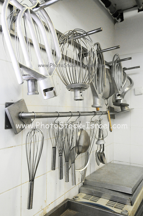 Industrial Bakery. Baker's Tools and equipment hanging on the wall before use