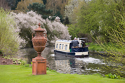 Terracotta urn by the canal with barge passing