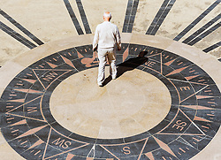 A man standing on a stylised compass at Cromer Prospect on Cromer seafront in Norfolk.