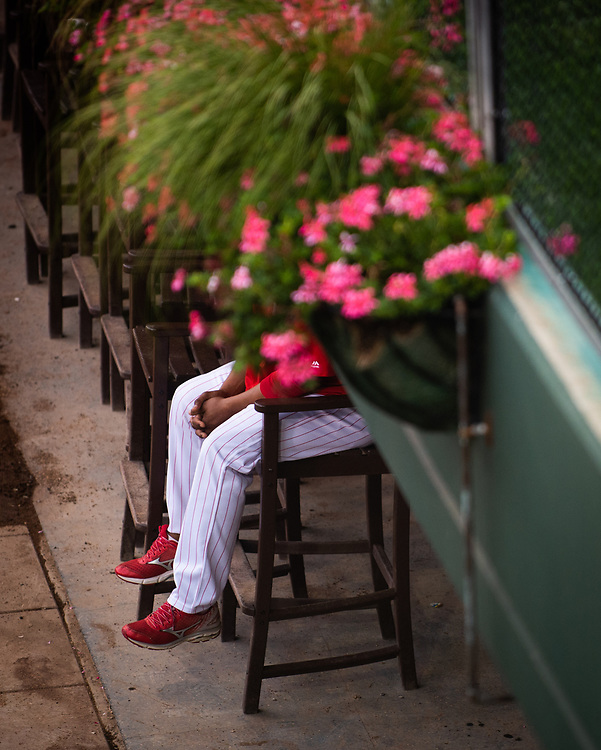 A Philadelphia Phillies pitching coach watches Phillies catcher Cameron Rupp warm up in the bullpen before facing the Atlanta Braves.