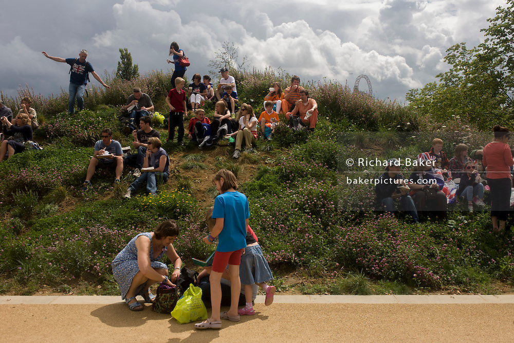 Families occupy a small hill that has the Orbit artwork tower in the background. during the London 2012 Olympics. Standing 115 metres high, the Orbit is the tallest art structure in Britain - offering views over the Olympic Stadium, Olympic Park and the whole of London. This land was transformed to become a 2.5 Sq Km sporting complex, once industrial businesses and now the venue of eight venues including the main arena, Aquatics Centre and Velodrome plus the athletes' Olympic Village. After the Olympics, the park is to be known as Queen Elizabeth Olympic Park.