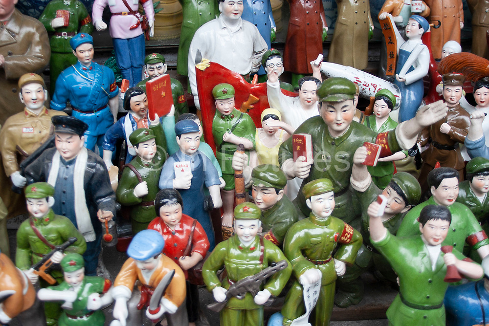 Figures from the Cultural revolution for sale at a stall on Dong Tai Road (Dongtai Lu) street market. This small area, dedicated to antiques is lined with shops and the streets covered with stalls selling artifacts from Shanghai's past. There are some genuine Chinese antiques which can be very expensive. But there are also a lot of fakes for sale too, like these figures. Usually snapped up by tourists who are under the impression they are getting a bargain.