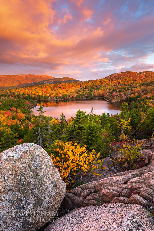 The Bowl, a mountain pond, surrounded by fall color with Cadillac Mountain seen in the background in Acadia National Park, Mount Desert Island, Maine.