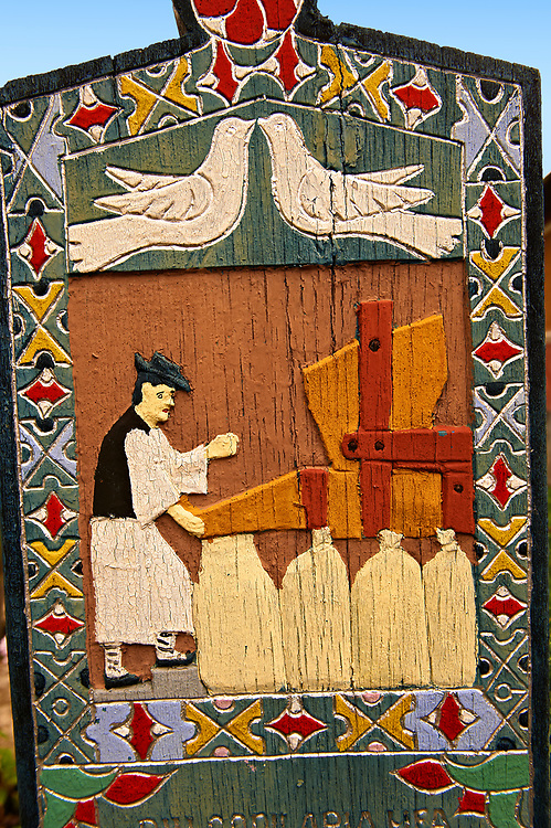 Tombstone showing a miller bagging corn, The  Merry Cemetery ( Cimitirul Vesel ),  Săpânţa, Maramares, Northern Transylvania, Romania.  The naive folk art style of the tombstones created by woodcarver  Stan Ioan Pătraş (1909 - 1977) who created in his lifetime over 700 colourfully painted wooden tombstones with small relief portrait carvings of the deceased or with scenes depicting them at work or play or surprisingly showing the violent accident that killed them. Each tombstone has an inscription about the person, sometimes a light hearted  limerick in Romanian. .<br /> <br /> Visit our ROMANIA HISTORIC PLACXES PHOTO COLLECTIONS for more photos to download or buy as wall art prints https://funkystock.photoshelter.com/gallery-collection/Pictures-Images-of-Romania-Photos-of-Romanian-Historic-Landmark-Sites/C00001TITiQwAdS8