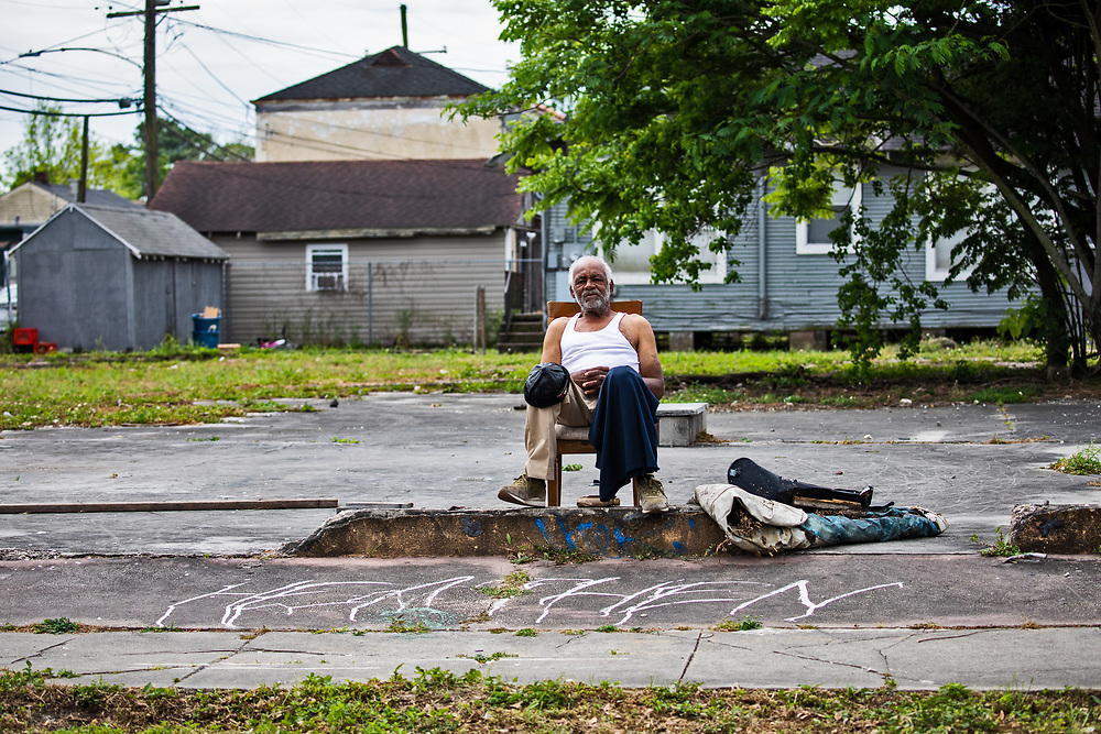 April 4, 2020, New Orleans, Louisiana - Man sitting by himself on St. Clause Ave, a main street in the Lower Ninth Ward in New Orleans while the COVID-19 Pandemic worsens.