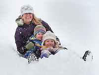 For Alyssa Milligan and her two daughters Kayley and Lilly it takes a couple of tries to pack down the freshly fallen snow as they enjoyed a morning of sledding at Memorial Park's sledding hill during Thursday's blizzard.  (Karen Bobotas/for the Laconia Daily Sun)