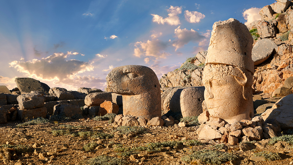 Statue heads at sunrise, from right,  Antiochus & Eagle  in front of the stone pyramid 62 BC Royal Tomb of King Antiochus I Theos of Commagene, east Terrace, Mount Nemrut or Nemrud Dagi summit, near Adıyaman, Turkey .<br /> <br /> If you prefer to buy from our ALAMY PHOTO LIBRARY  Collection visit : https://www.alamy.com/portfolio/paul-williams-funkystock/nemrutdagiancientstatues-turkey.html<br /> <br /> Visit our CLASSICAL WORLD HISTORIC SITES PHOTO COLLECTIONS for more photos to download or buy as wall art prints https://funkystock.photoshelter.com/gallery-collection/Classical-Era-Historic-Sites-Archaeological-Sites-Pictures-Images/C0000g4bSGiDL9rw
