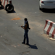 A local resident takes guard at a checkpoint in Gargaresh neighbourhood in central Tripoli.