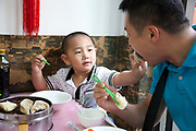 A family has Chinese dumplings for breakfast in a small restaurant in Xuanwu district, an area just south of Tiananmen in Beijing, China.