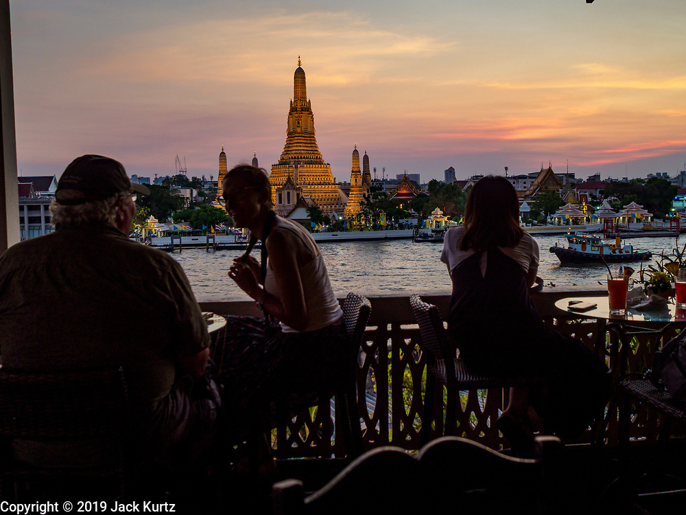 """06 MARCH 2019 - BANGKOK, THAILAND:  Tourists watch the sunset on Wat Arun. Wat Arun Ratchawararam Ratchawaramahawihan or Wat Arun (""""Temple of Dawn"""") is a Buddhist temple (wat) in Bangkok on the Thonburi side of the Chao Phraya River. The temple derives its name from the Hindu god Aruna, who is personified as the rising sun. Wat Arun is among the best known of Thailand's temples. The temple has existed since at least the seventeenth century, but its distinctive prang (spires) were built in the Khmer style in the early nineteenth century during the reign of King Rama II.  PHOTO BY JACK KURTZ"""