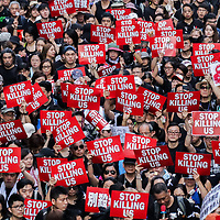 """A sea of protesters exhibiting """"Stop Killing Us"""" signs during June protests in Hong Kong. Protesters are opposed to a controversial extradition bill."""