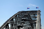 Top of the arch of the Sydney Harbour Bridge. Groups of tourists can be seen climbing the bridge. Sydney, Australia