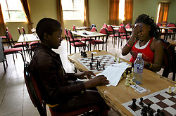 Phiona Mutesi, left, a 14-year-old chess prodigy, shares a laugh with her opponent during a match, in Kampala, Uganda, Dec. 11, 2010. Mutesi lives in the slums of Uganda and is just now learning to read. But her instincts have made her a player to watch in international chess. Mutesi, a naturally talented chess player is coached by Robert Katende of Sports Outreach Ministry. The chess club meets at the Agape Church inside Katwe, the largest slum in Kampala.