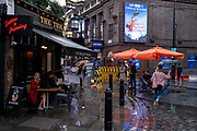 On a rainy night in Soho, Londoners use a pedestrianised Old Compton Street at a time when recently re-opened bars and restaurants are desperate for customer business during the coronavirus pandemic, on 27th August 2020, in London, England.