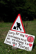 "Balcombe, West Sussex. Site of Cuadrilla drilling . A placard, next to a 'Men working"" roadsign says 'Sorry for the inconvenience. We are trying to Save the Planet'."