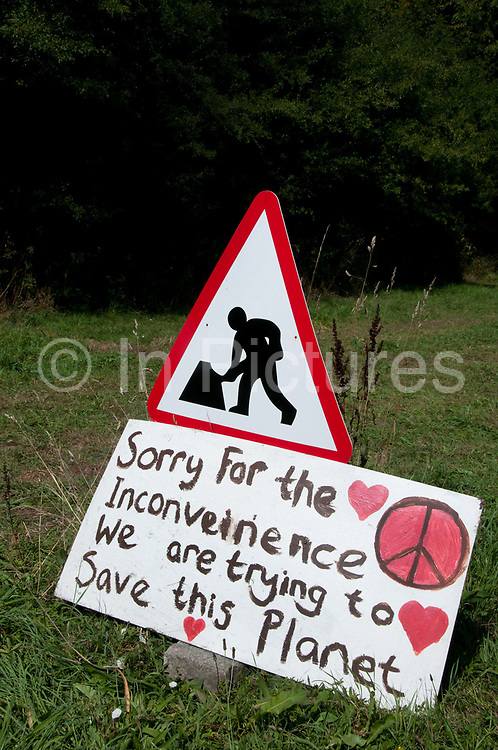 """Balcombe, West Sussex. Site of Cuadrilla drilling . A placard, next to a 'Men working"""" roadsign says 'Sorry for the inconvenience. We are trying to Save the Planet'."""