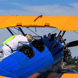 A pilot checks the cockpit of the blue and yellow biplane  at the Lancaster Airport Community Days air show.