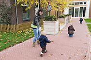 Nederland, Helmond, 20091111...Kinderdagverblijf de Bereboot is een nieuw kdv dat is gestart op een landgoed in een mooie ruime en groene omgeving. ..De laan naar de kinderopvang. Kleine kinderen met de juf.....Netherlands, Helmond, 20091111. ..Childcare, The nursery the Bear boot is on an estate in a beautiful and spacious green surroundings.