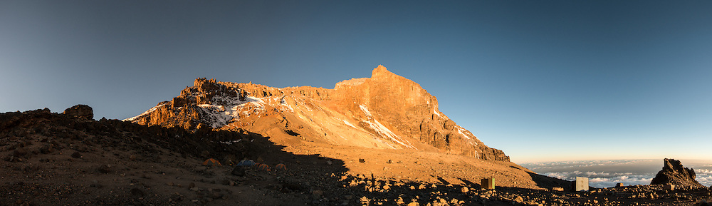 A panorama just before sunset of the rugged and steep Western Breach as seen from Arrow Glacier Camp on Mt Kilimanjaro's Lemosho Route. The campsite is in the shade at left.