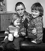 Mrs Roisin Fox, 20 years, Churchill Park, Portadown, Craigavon, N Ireland, who was beaten up and had her hair shorn when three masked men broke into her home. They claimed she was a police informer and gave her 48 hours to leave or be shot. She is pictured with her children Geraldine, 2 years, and Tony, 4 years. 197401170019b.<br /> <br /> Copyright Image from Victor Patterson, Belfast, UK<br /> <br /> t: +44 28 9066 1296 (from Rep of Ireland 048 9066 1296)<br /> m: +44 7802 353836<br /> e: victorpattersonbelfast@gmail.com<br /> <br /> www.images4media.com<br /> <br /> Please see my full Terms and Conditions of Use at https://www.images4media.com/p/terms-conditions - it is IMPORTANT that you familiarise yourself with them.<br /> <br /> Images used online incur an additional cost. This cost should be agreed in writing in advance. Online images must be visibly watermarked i.e. © Victor Patterson or that of the named photographer within the body of the image. The original metadata must not be deleted from images used online.<br /> <br /> This image is only available for the use of the download recipient i.e. television station, newspaper, magazine, book publisher, etc, and must not be passed on to a third party. It is also downloaded on condition that each and every usage is notified within 7 days to victorpattersonbelfast@gmail.com.<br /> <br /> The right of Victor Patterson (or the named photographer) to be identified as the author is asserted in accordance with The Copyright Designs And Patents Act (1988). All moral rights are asserted.