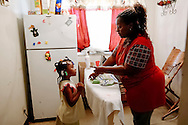 Anita Perkins talks to her daughter, Jeoria Gilliam, 4, as she irons clothes at their apartment in Alorton, Illinois. Perkins works two jobs as a nurse to try to support herself and her three children.