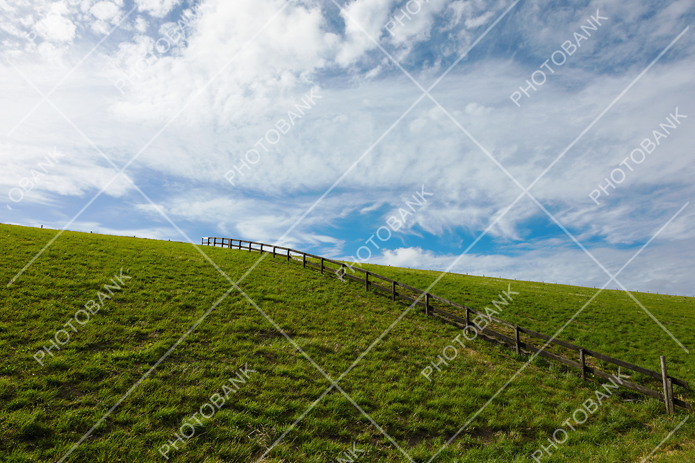 Green hill with fence in the plain of the Netherlands