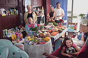The Sobczynscy family in the main room of their apartment in Konstancin-Jeziorna; Poland; outside Warsaw; with a week's worth of food. Marzena Sobczynska; 32; and Hubert Sobczynski; 31; stand in the rear; with Marzena's parents; Jan Boimski; 59; and Anna Boimska; 56; to their right and their daughter Klaudia; 13; on the couch. From the book Hungry Planet: What the World Eats (Model Released)