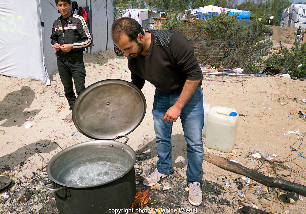 Young man from Afganistan boiling a large pot to make a meal in Calais Jungle Migrant and Refugee Camp