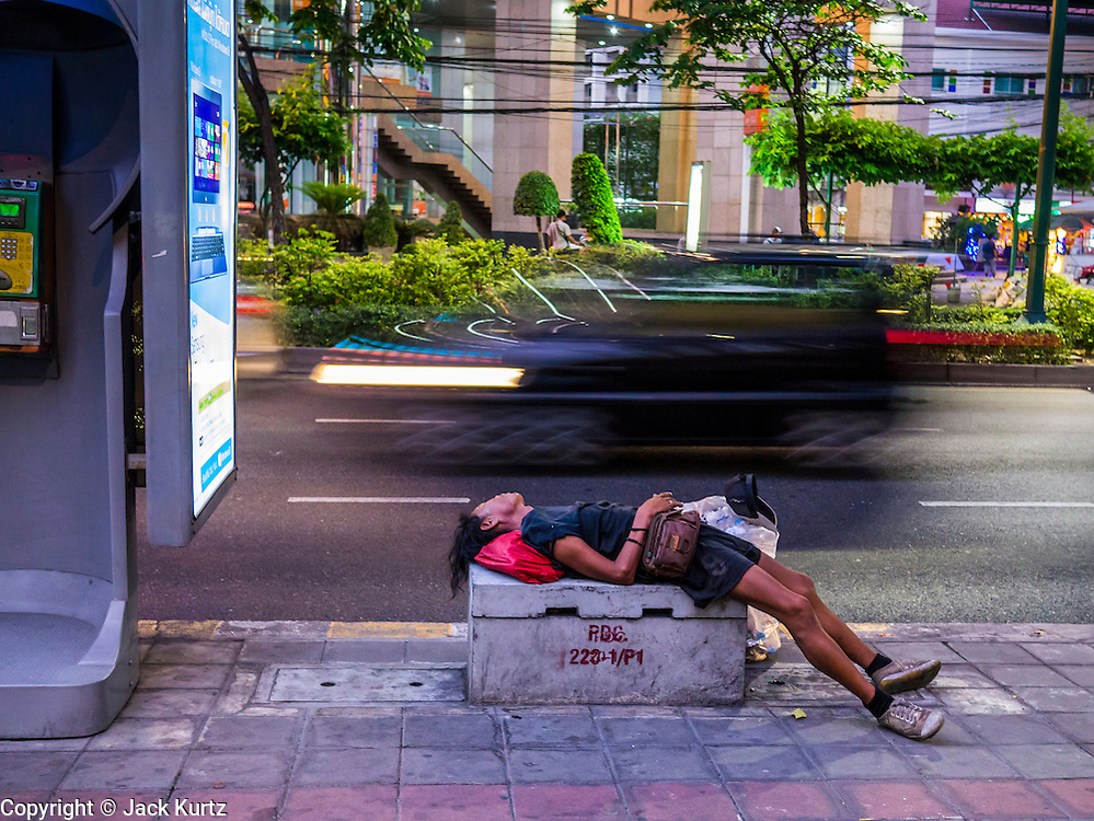 """30 MARCH 2013 - BANGKOK, THAILAND:  A man sleeps on a concrete block on Sukhumvit Road in Bangkok. Thailand's economic expansion since the 1970 has dramatically reduced both the amount of poverty and the severity of poverty in Thailand. At the same time, the gap between the very rich in Thailand and the very poor has grown so that income disparity is greater now than it was in 1970. Thailand scores .42 on the """"Ginni Index"""" which measures income disparity on a scale of 0 (perfect income equality) to 1 (absolute inequality in which one person owns everything). Sweden has the best Ginni score (.23), Thailand's score is slightly better than the US score of .45.  PHOTO BY JACK KURTZ"""