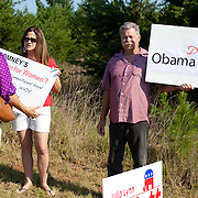 A husband and wife hold up pro-Obama signs outside of a Mitt Romney rally in Charlotte, NC during the 2012 presidential primaries.
