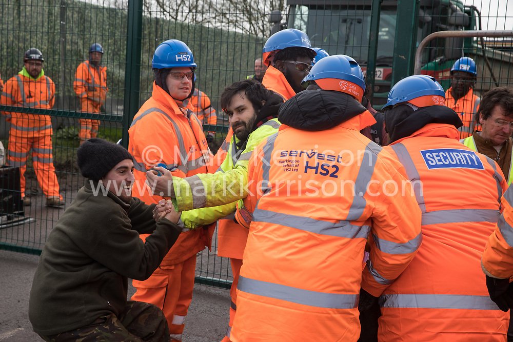 Harefield, UK. 8 February, 2020. HS2 engineers try to prevent environmental activists from Save the Colne Valley, Stop HS2 and Extinction Rebellion from accessing an area of Harvil Road fenced off in order to carry out tree felling works for the high-speed rail project. The activists were successful in preventing any of the scheduled tree felling by HS2 and after an intervention by a police officer all tree felling work has now been cancelled for the weekend.
