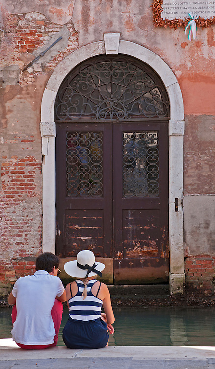 Couple relaxing by the canal, Venice.