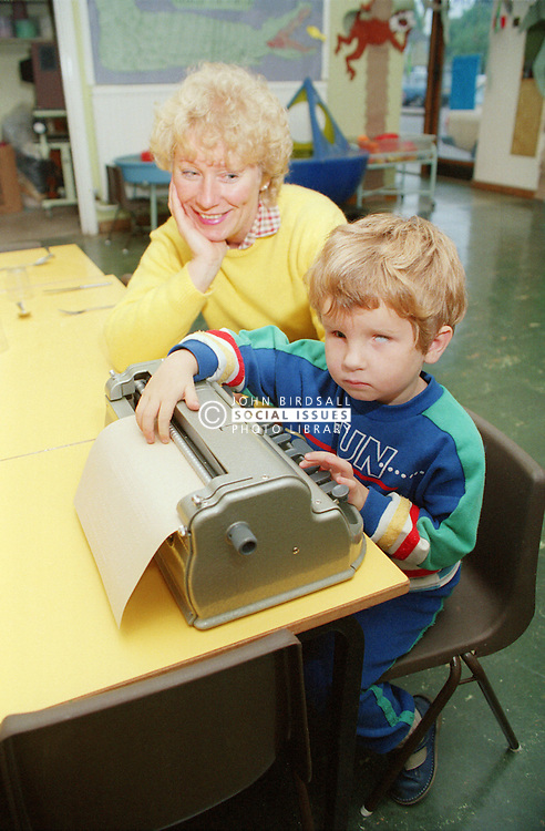 Teacher sitting at desk in classroom teaching young boy with visual impairment to type and read using adapted Braille typewriter,
