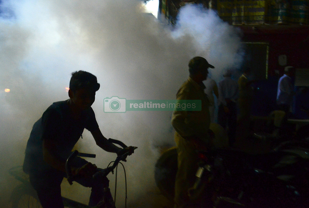 November 1, 2018 - Allahabad, India - Indian people walk past smoke from fumigation being carried out to prevent the spread of mosquito-borne diseases in Allahabad, India, on November 1,2018. More than 200 million people live in impoverished Uttar Pradesh, India's most populous state. Thousands of people suffer from encephalitis, malaria, typhoid and other mosquito-borne diseases each year during the winter monsoon. (Credit Image: © Ritesh Shukla/NurPhoto via ZUMA Press)