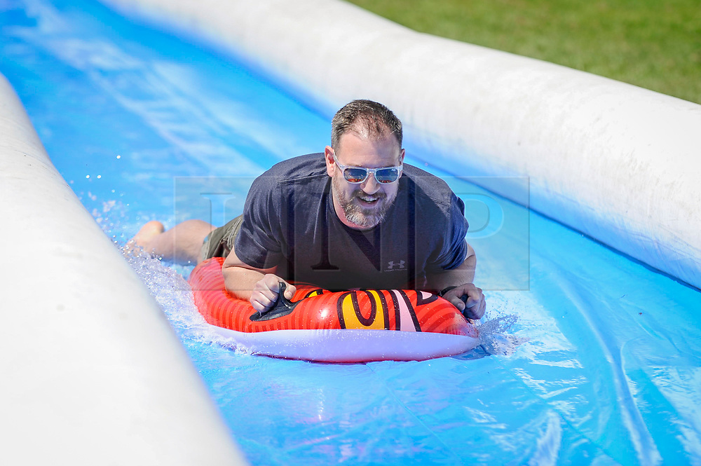 © Licensed to London News Pictures. 06/05/2018. CHESHAM, UK.  A rider keeps cool on a hot day sliding down the inaugural Lowndes Slide, a 100m water slide, in Chesham, Buckinghamshire, with each ride raising money for local charities.  Forecasters predict that the Bank Holiday Monday will be even warmer.  Photo credit: Stephen Chung/LNP
