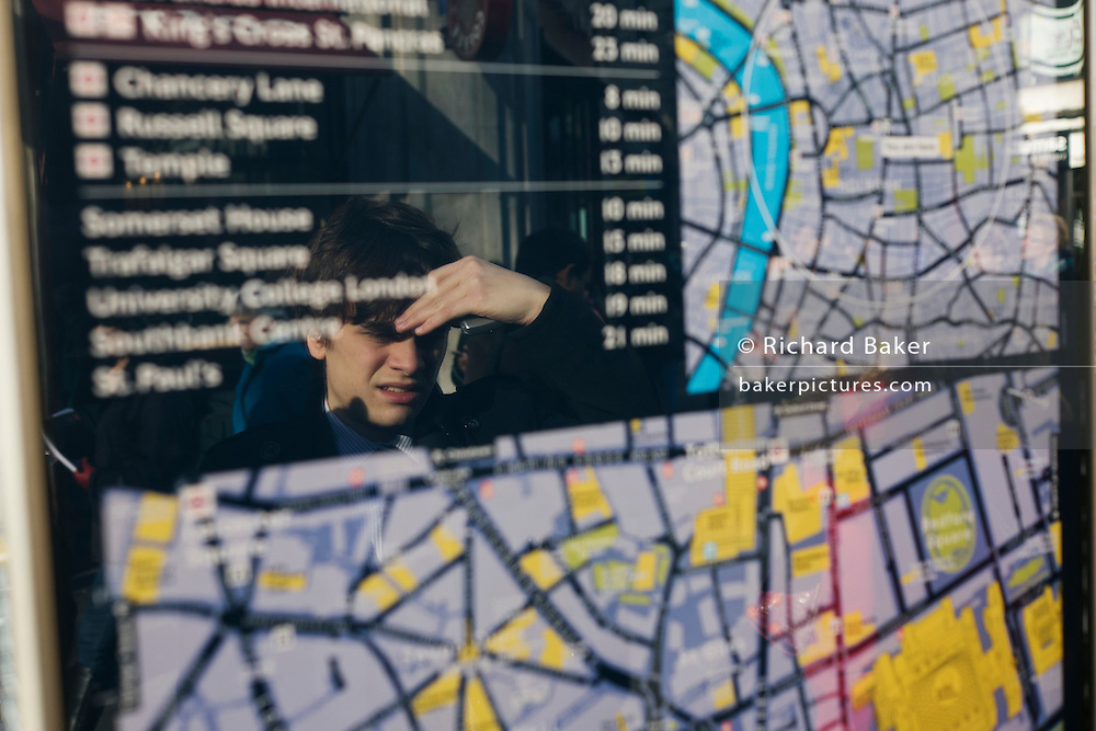A visitor examines one of the many street maps of central London, this one located outside Holborn station.