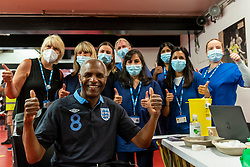 """© Licensed to London News Pictures. 27/06/2021. WATFORD, UK. Former Watford player Luther Blissett poses with medical staff at a pop-up mass vaccination clinic at Watford FC's Vicarage Road Stadium as part of the """"Grab a jab"""" campaign. The NHS is also promoting a number of walk-in clinics this weekend across the capital to try to increase the number of over 18s receiving a jab as cases of the Delta variant are reported to be on the rise..  Photo credit: Stephen Chung/LNP"""